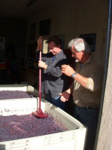 Tom counsels C on the correct procedure for punching down the grapes. Even the air is full of wine here.